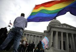 "Gay-rights supporter Mathew ""Skippy"" Mauldin holds a flag during a gay rights rally outside the Capitol in Jefferson City, Mo."
