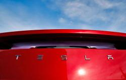In this April 15, 2018 file photo, the sun shines off the rear deck of a roadster on a Tesla dealer's lot in the south Denver suburb of Littleton, Colo.