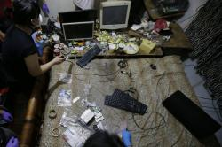 In this April 20, 2017, file photo, members of the National Bureau of Investigation and FBI gather evidence at the home of an American suspected child webcam cybersex operator during a raid in Mabalacat, Philippines