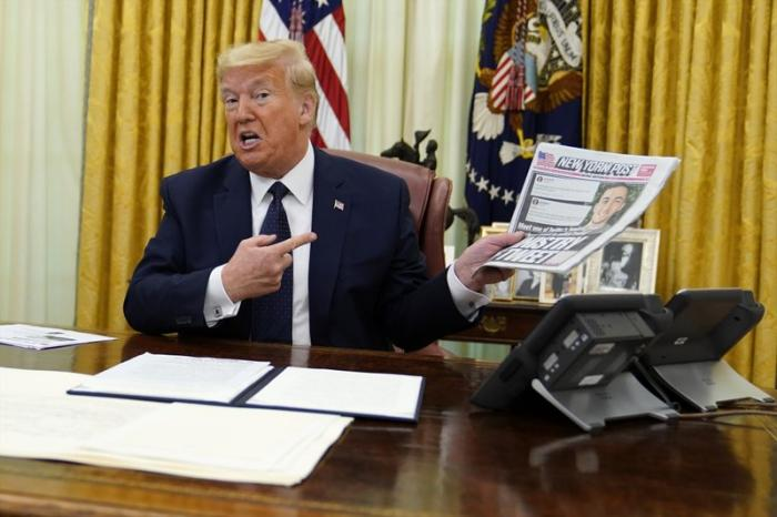 President Donald Trump holds up a copy of the New York Post as he speaks before signing an executive order aimed at curbing protections for social media giants, in the Oval Office of the White House, Thursday, May 28, 2020, in Washington