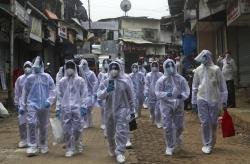 Health workers arrive to administer a medical camp in a slum in Mumbai, India.