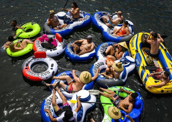 A group of at least 15 people float on connected inflatables down the American River in the Sunrise Recreation Area near Rancho Cordova, Calif.