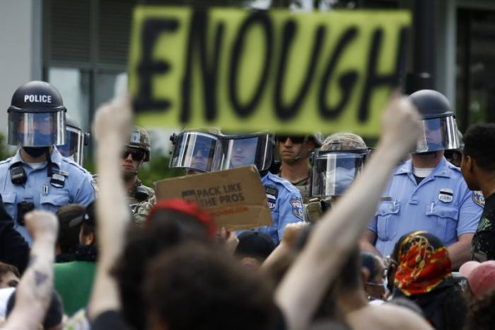 In this June 1, 2020, file photo, protesters rally as Philadelphia Police officers and Pennsylvania National Guard soldiers look on in Philadelphia, over the death of George Floyd, a black man who was in police custody in Minneapolis
