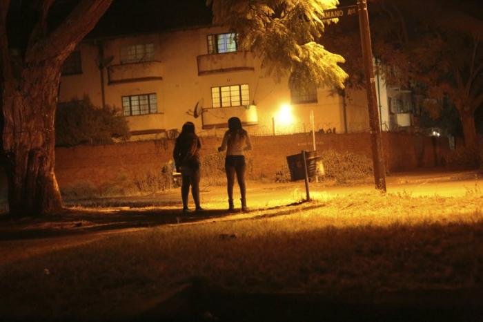 Sex workers wait for clients in the red light district of Harare, Zimbabwe, Friday, June 12, 2020
