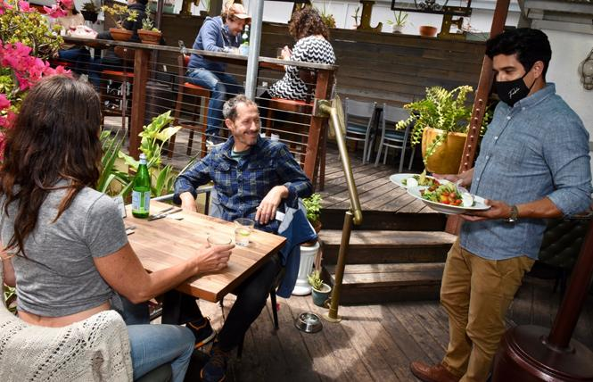 Ramsey Garcia, right, co-owner of Fable, serves Katie Brillault and Rick Holthouse on the patio of the restaurant