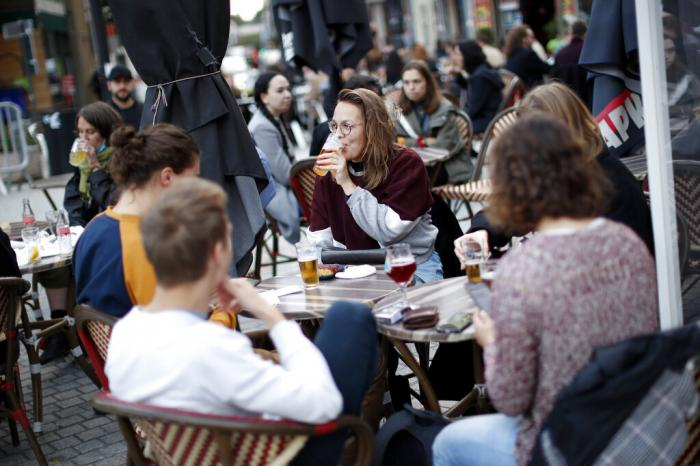 People drink beers on a terrace of a pub on the last evening before bars were closed in Brussels.