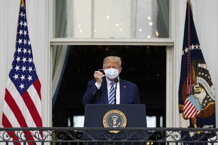 President Donald Trump removes his face mask to speak from the Blue Room Balcony of the White House to a crowd of supporter