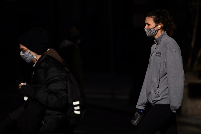 People wearing face masks cross Broad Street in Philadelphia.