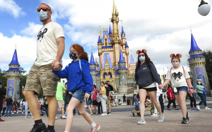 A family walks past Cinderella Castle in the Magic Kingdom, at Walt Disney World in Lake Buena Vista, Fla.