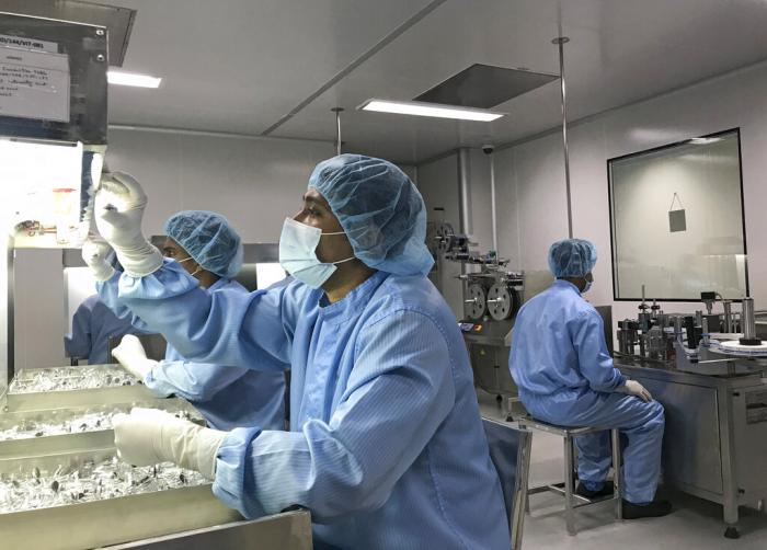 Production personnel perform a visual inspection of filled vaccine vials inside the Incepta plant on the outskirts of Dhaka in Bangladesh.