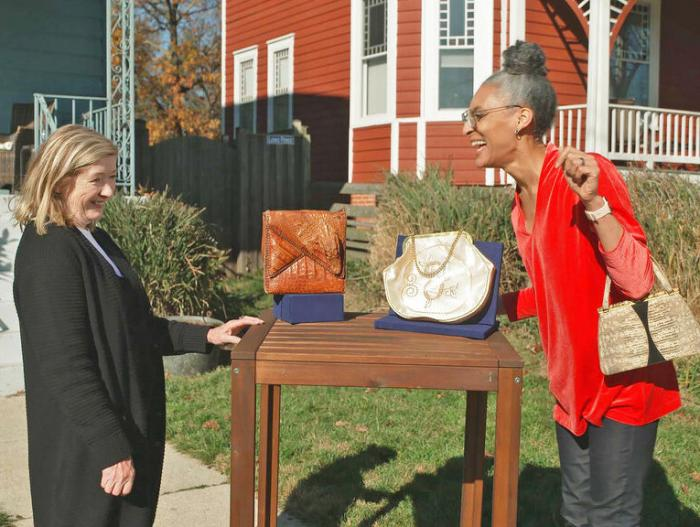 """This image released by WGBH-TV shows Katy Kane, left, as she appraises celebrity chef Carla Hall's vintage purse collection in an episode of """"Antiques Roadshow Celebrity Edition,"""" airing May 10 on PBS."""