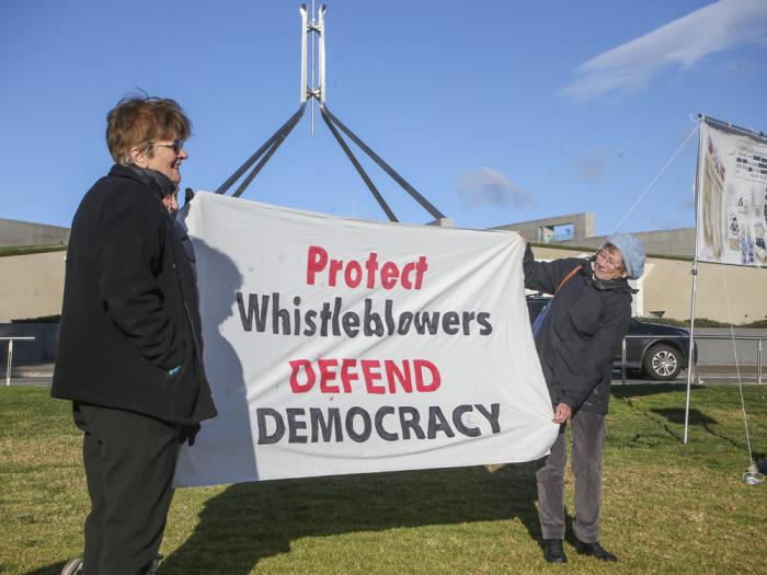 Demonstrators hold a banner during a protest outside Parliament House in Canberra, Australia, Thursday, June 17, 2021 against the prosecution of lawyer Bernard Collaery.
