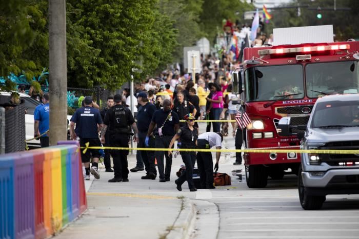 Police and firefighters respond after a truck drove into a crowd of people during The Stonewall Pride Parade and Street Festival in Wilton Manors, Fla., on Saturday, June 19, 2021