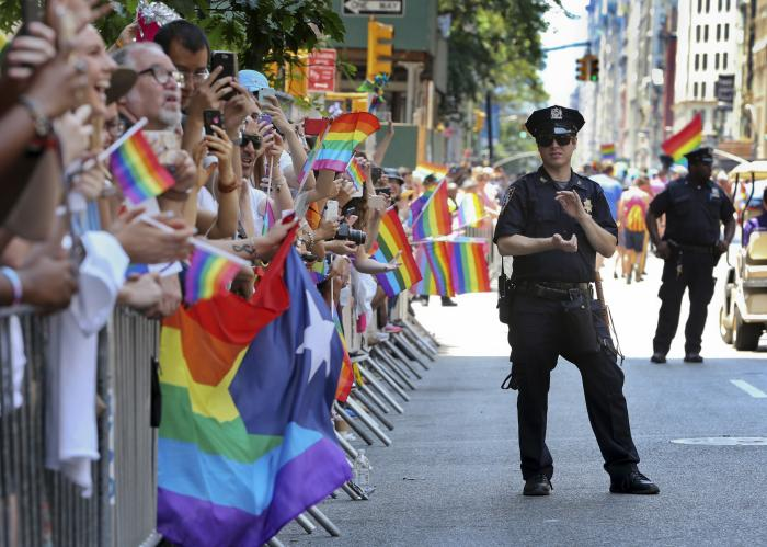 A police officer applauds as parade-goers shout and wave flags during the New York City Pride Parade, Sunday, June 26, 2016 in New York.