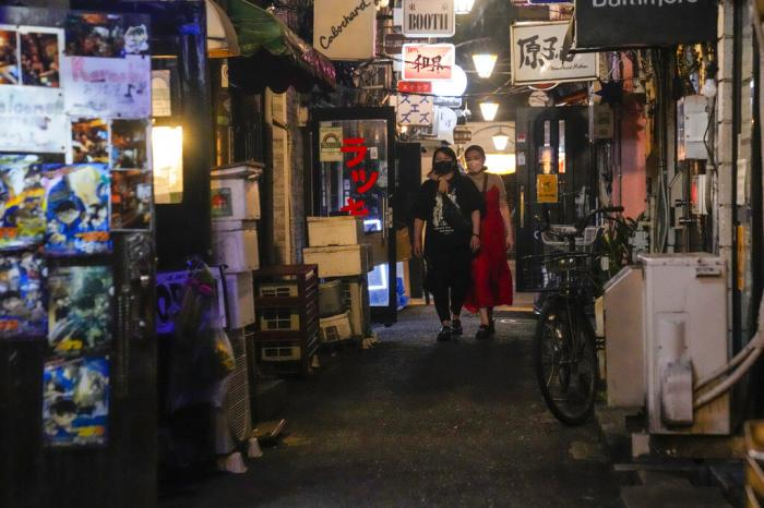 People walk around and gather at a bar after government imposed 8 p.m. closing time for restaurants and bars under Tokyo's fourth state of emergency.