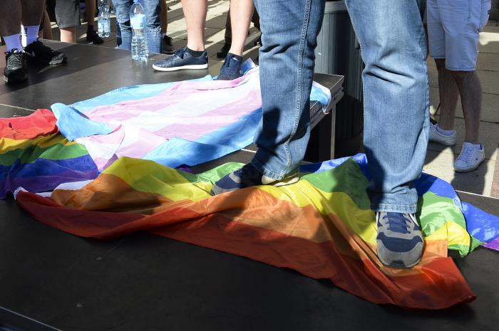 A man stands on a Rainbow Flag as he attends a demonstration of far-right activists against LGBT rights in Warsaw, Poland.